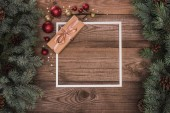 pohled shora bílý rámeček, vánoční dárek a lesklé cetky na dřevěný povrch s jedle větvičky a šišky