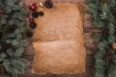 kus pergamenu s větvičky jedle, lesklé cetky a šišky na dřevěné pozadí