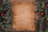 Detailní zobrazení prázdného pergamenu s větvičky jedle, lesklé cetky a šišky na dřevěné pozadí