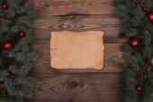 pohled shora prázdného pergamenu s větvičky jedle, lesklé cetky a šišky na dřevěné pozadí