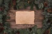pohled shora kus pergamenu a jehličnaté větve s šišky na dřevěné pozadí