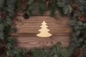 pohled shora krásné vánoční strom symbol a jehličnaté větve s šišky na dřevěné pozadí