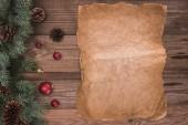 pohled shora kus pergamenu, jehličnaté větve, šišky a ozdoby, Vánoční pozadí