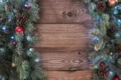 Fotografia vista superiore dei ramoscelli di conifere con splendente bagattelle, pigne e illuminate garland, priorità bassa di Natale