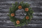 Photo top view of beautiful christmas wreath with pine cones on wooden background