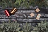 Fotografie pohled shora krásné jedle stálezelených větviček, dárkové krabičky a lesklé stuhy na dřevěné pozadí