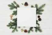 top view of blank white card with evergreen twigs, pine cones and golden christmas balls