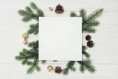 pohled shora prázdné bílé karty s stálezelené větvičky, šišky a zlatý vánoční koule