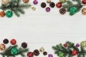 pohled shora barevné vánoční kuličky, jedle větvičky a šišky na bílém pozadí dřevěná