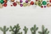 pohled shora lesklé barevné koule a větvičky zelené jedle na dřevěný povrch, Vánoční pozadí