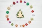 Fotografie pohled shora jehličnaté větvičky, stromeček symbolu a barevné lesklé cetky na dřevěný povrch