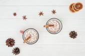 Photo top view of cups with hot chocolate and marshmallows, cinnamon sticks, star anise and pine cones on wooden table