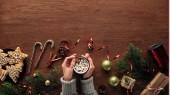 Fotografie částečný pohled shora osoby držící šálek s horkou čokoládou a marshmallows, soubory cookie, spořádáme a vánoční ozdoby na dřevěné pozadí