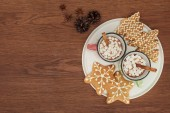 Photo top view of cups with hot chocolate and marshmallows, cinnamon sticks and gingerbread cookies on wooden table