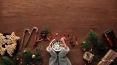 Fotografie oříznutý snímek osoby držící šálek kakaa a marshmallows, soubory cookie, candy hole a vánoční ozdoby na dřevěné pozadí