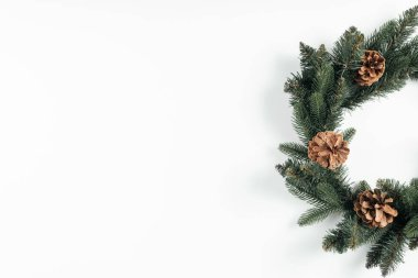 close-up view of beautiful christmas wreath with pine cones on white background