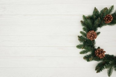 top view of beautiful christmas wreath on white wooden background