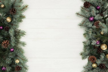 beautiful evergreen fir twigs with shiny baubles and pine cones on white wooden background