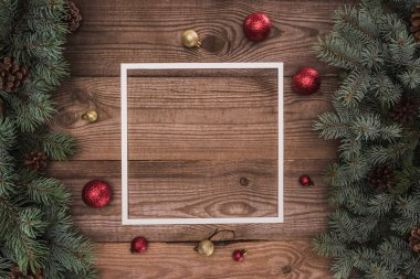 white frame, shiny red and golden balls and coniferous branches with pine cones, christmas background