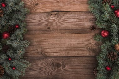 top view of beautiful evergreen fir twigs with shiny balls and pine cones on wooden background