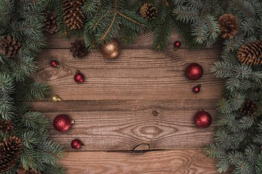 top view of shiny red and golden balls, fir twigs and pine cones on wooden background