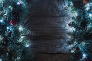top view of beautiful christmas tree branches with baubles, pine cones and illuminated garland on wooden background