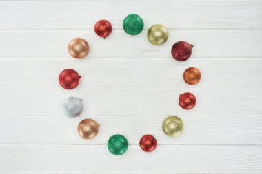round frame made of beautiful colorful christmas balls on white wooden surface
