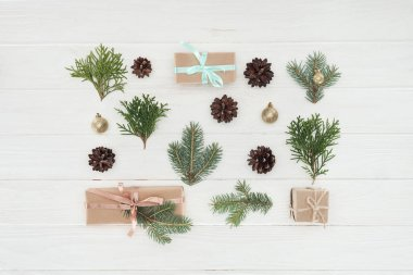 top view of christmas presents, evergreen coniferous branches and pine cones on wooden surface
