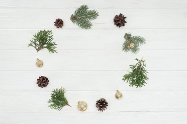 top view of evergreen coniferous twigs, pine cones and golden baubles on wooden background