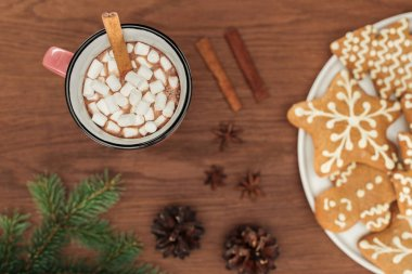 top view of cup with hot chocolate and marshmallows, cinnamon sticks and gingerbread cookies