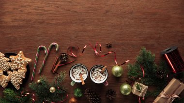 top view of mugs with hot chocolate, marshmallows and cinnamon sticks and christmas decorations on wooden background