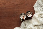 Photo top view of mugs with delicious hot chocolate, marshmallows and cinnamon sticks on wooden background