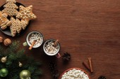 Photo flat lay with cups with hot chocolate, marshmallows and cinnamon sticks, tasty cookies and fir twigs with shiny baubles on wooden surface, christmas background