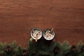 Photo top view of cups with hot chocolate, marshmallows and cinnamon sticks on wooden background