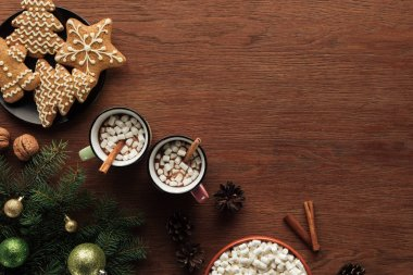 flat lay with cups with hot chocolate, marshmallows and cinnamon sticks, tasty cookies and fir twigs with shiny baubles on wooden surface, christmas background