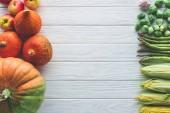 pohled shora růžičkovou kapustu, zelený chřest, kukuřičné klasy, česnek a dýně na dřevěný stůl