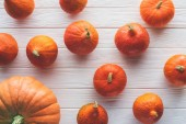 Photo top view of scattered autumnal orange pumpkins on wooden tabletop