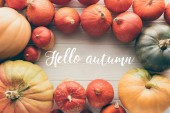 Fotografie top view of ripe pumpkins on tabletop with words Hello Autumn