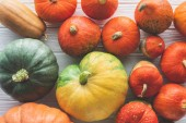 Fotografie top view of pile of ripe autumnal pumpkins on wooden tabletop
