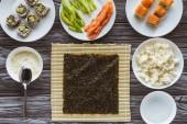 pohled shora nori a chutné ingredience pro vaření sushi na dřevěný stůl