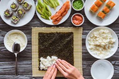 partial top view of person preparing sushi with rice, nori and ingredients