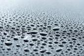 Fotografie zblízka pohled kapky vody na šedém povrchu jako pozadí