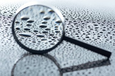 close up view of magnifying glass and water drops on grey backdrop