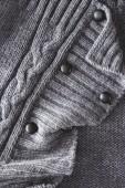 zblízka pohled šedé pletené látky s tlačítky jako pozadí