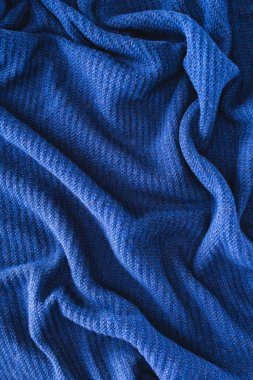 full frame of blue folded woolen fabric as background