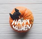 Fotografie pohled z dýně s domácí halloween cookie na dřevěný stůl s nápisem happy halloween