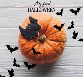 Fotografie pohled na dýně s domácí halloween cookie na vyvýšeném místě na dřevěný stůl s Moje první halloween nápisy