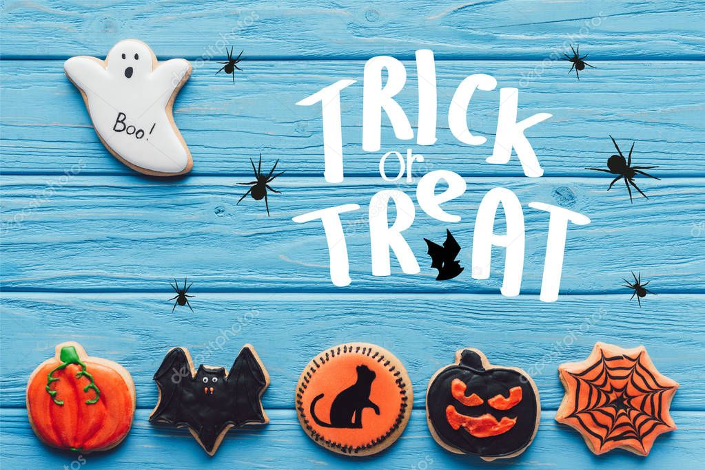 """Elevated view of spooky halloween cookies on blue wooden background  with """"trick or treat"""" lettering"""