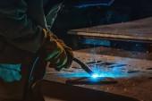 částečný pohled svářečka v ochranné masce svařování kovů s jiskry v továrně