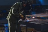 Fotografie koncentrovaný výrobě dělník svařování kovů s jiskry v továrně